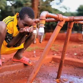 A Young Sportsman Drinks Water From The Pump After His Training